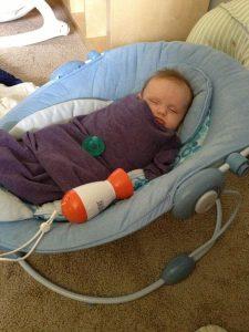 bébé dormant dans un landau à coté du baby shusher